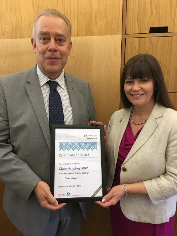 Simon Hodgson of Carers Scotland presenting accreditation to Clare Haughey MSP